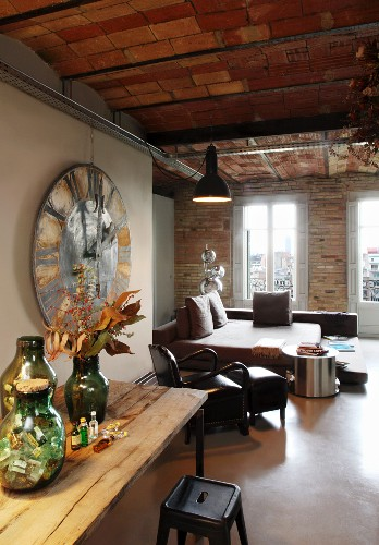 Group of vases on wooden table, 50s-style metal stool and living and sleeping areas in background in rustic interior with brick wall and ceiling