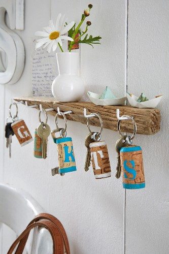 A key board made from driftwood and keys with homemade key rings made from corks painted with letters