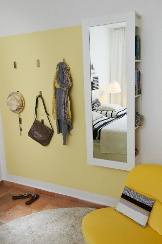 Useful hooks on pale yellow wall panel next to mirror with concealed storage space in bedroom