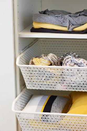Pretty wire baskets used as tidy storage solution in wardrobe