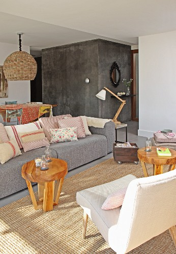 Grey couch and round wooden side tables on sisal rug in lounge area of open-plan interior