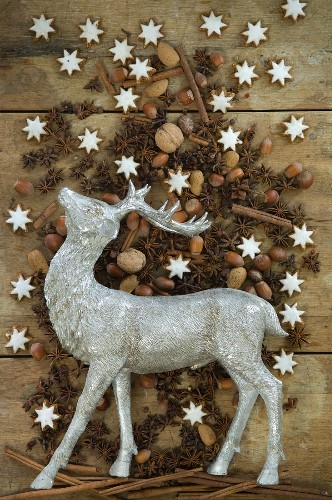 Stag figurine surrounded by nuts, cinnamon stars, cinnamon sticks and star anise