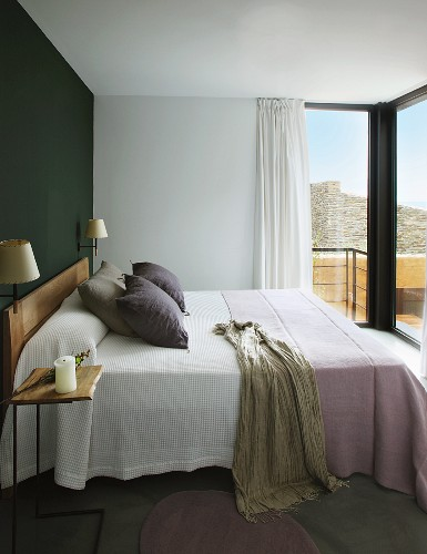 Double bed with pale blankets against dark accent wall in modern bedroom
