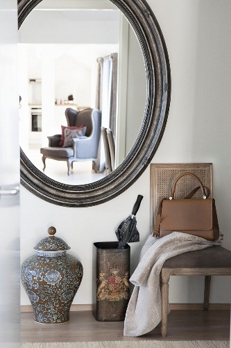 Upholstered chair, umbrella stand, floor vase and oval vase in hallway