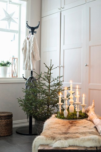 Animal-skin rug on bench, candles on tray of moss, small Christmas tree and fitted cupboards in background
