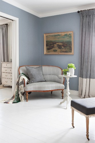Biedermeier sofa with pale grey cover below antique painting on dove blue wall in elegant interior