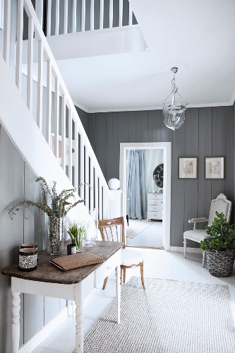 Elegant hallway with white-painted wooden staircase and grey wood-clad walls