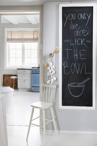 Message on blackboard in white foyer and view into kitchen with lattice window and vintage ambiance
