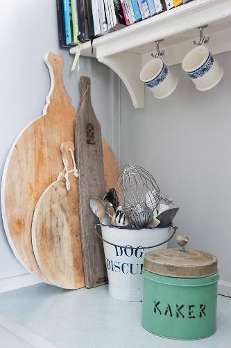 Vintage tin, metal bucket of kitchen utensils and wooden chopping boards on kitchen base unit below bracket shelf