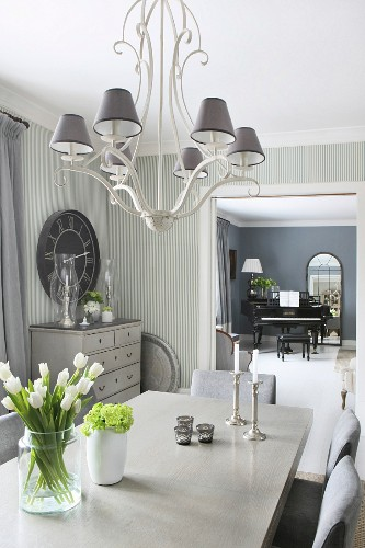 Elegant dining room in shades of grey with view of black piano in music room