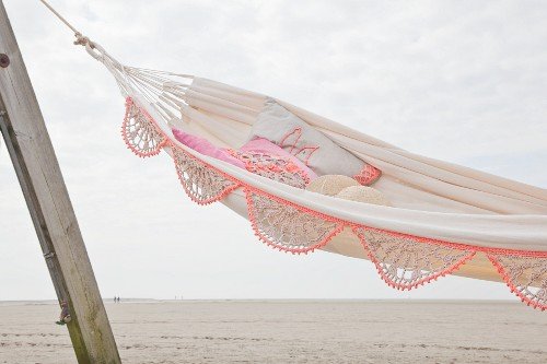 Hammock with crocheted trim hung on wooden posts