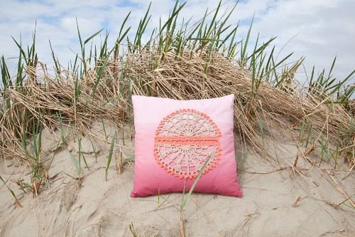 Kissen mit gehäkeltem Motiv auf Bezug und Farbverlauf in Pink am Sandstrand