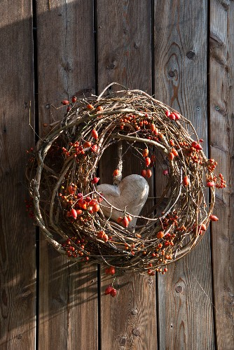 Wreath of berries, branches and rose hips with wooden love-heart in centre hung on wooden wall