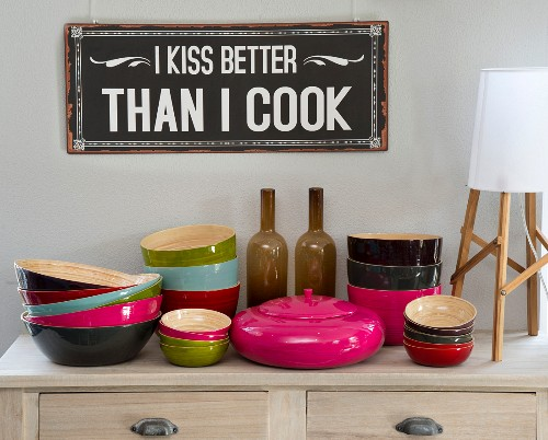 Colourful bamboo bowls and container with lid on wooden lowboy below sign with humorous motto on wall