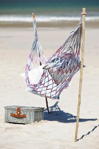 Hammock attached to sticks stuck in sandy beach next to picnic basket