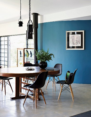 Classic shell chairs around oval wooden table in front of curved blue wall
