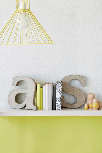 Decorative concrete letters used as bookends on shelf on wall