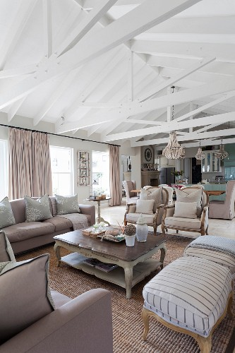 Polstermöbel um Couchtisch unter sichtbarere Dachkonstruktion in offenem Wohnraum