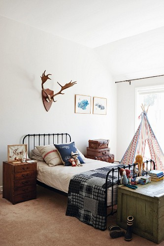 Country-house-style boy's room with black metal bed