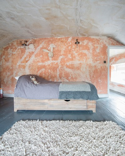 Soft toy on child's bed with drawers below in purist, renovated attic room with patinated walls and ceiling
