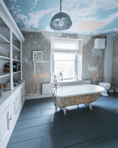 Free-standing vintage bathtub in large bathroom with shelving and patinated walls and ceiiling