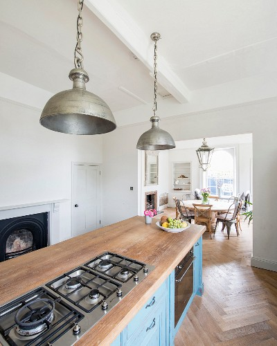 Vintage metal pendant lamps above free-standing kitchen counter with blue, patinated, country-house base units and oak worksurface