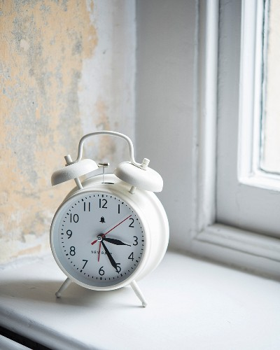 White, retro-style alarm clock on windowsill and wall with vintage patina