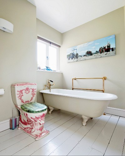 Ornate, antique toilet next to free-standing vintage bathtub on white-painted wooden floor of bathroom with walls painted pale grey