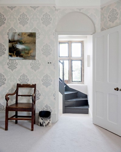 Antique armchair against wall with ornate wallpaper and view of winding wooden staircase through open door