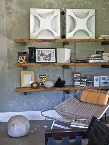Seating area below wooden shelves on grey concrete wall