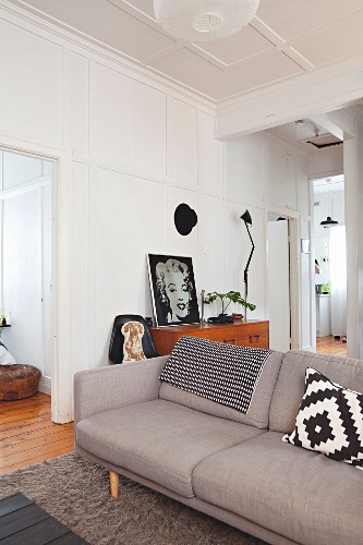 Retro sofa in panelled period apartment with portrait of Marilyn Monroe on top of chest of drawers