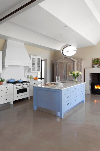Island counter with blue drawer fronts and marble worksurface in elegant, country-house kitchen with grey resin floor