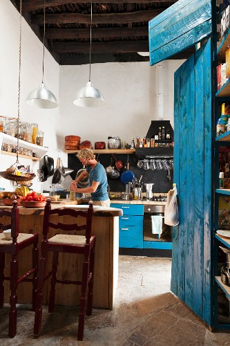Counter and bar stools in kitchen next to blue-painted cupboard; man in background