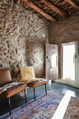 Brown leather chairs against stones wall and light falling on rug through open door in background