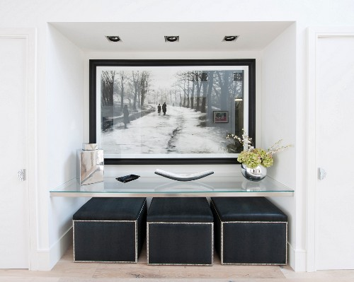 Large black and white picture in niche above glass shelf and black pouffes