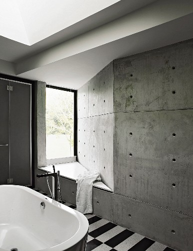 Bench integrated into concrete wall with anchor holes in bathroom