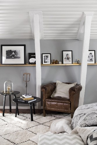 Leather armchair and side table below pictures on narrow shelf and sloping ceiling