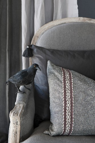 Antique grey armchair with scatter cushion and crow figurine on armrest