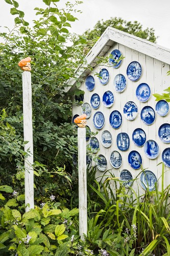 White gable-end wall of wooden cabin decorated with blue plates and ornamental wooden posts in garden