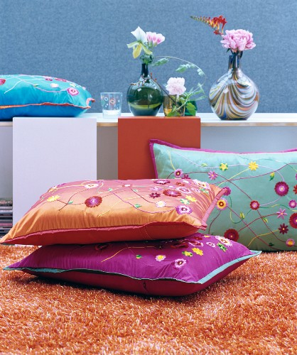 Decorative, colourful, floral scatter cushions on orange woollen rug in front of retro vases and flowers on sideboard