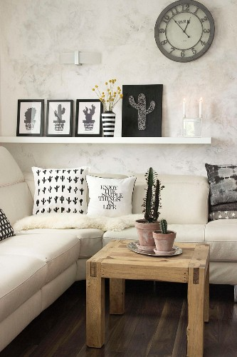 Cacti in terracotta pots and string art picture in corner of living room
