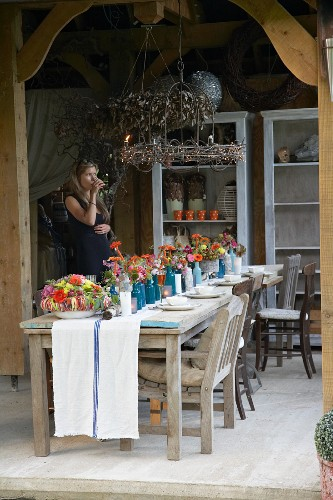 Rustic wooden table decorated with autumn flowers on roofed terrace with woman in background