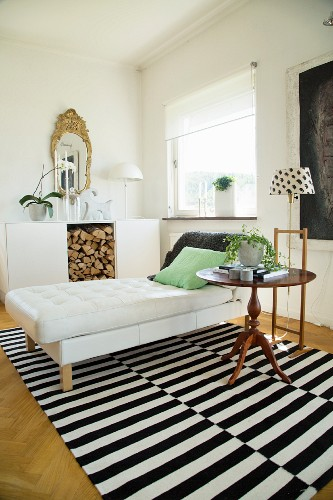 Modern chaise, standard lamp and antique side table on striped rug in front of firewood storage compartment