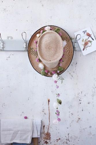 Strohhut dekoriert mit sommerlicher Blütengirlande an Garderobenleiste