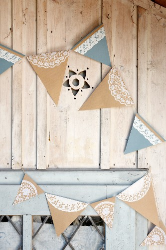 Hand-made bunting with lace trim on wooden façade of garden shed