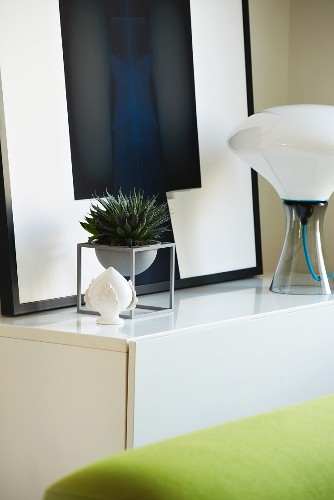 Framed picture, house plant and designer table lamp on white sideboard