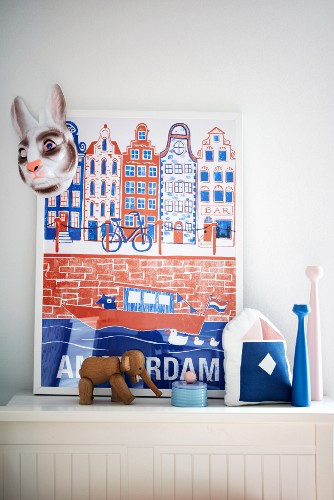 Framed poster, rabbit mask, elephant ornament and candlesticks on white wooden surface