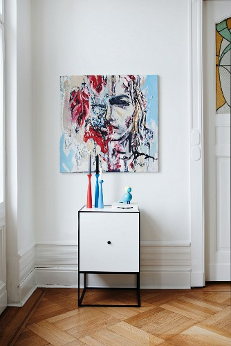Candlesticks on white cabinet below modern painting