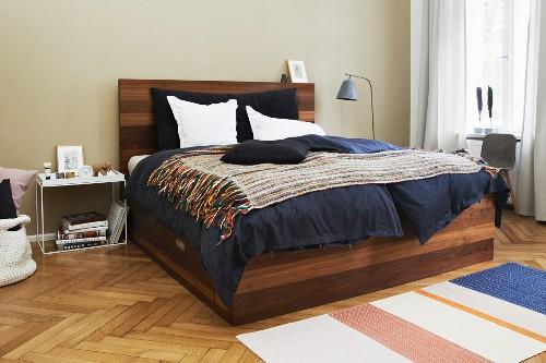Elegant wooden bed with integrated storage drawer on herringbone parquet floor
