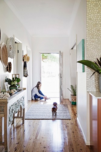 Entrance area with shiny floorboards, in the background girl in front of an open door with a dachshund on a carpet runner
